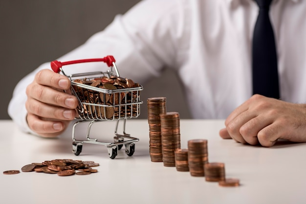 Front view of businessman holding shopping cart with coins Free Photo