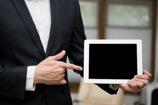 Front view of businessman pointing at tablet Free Photo