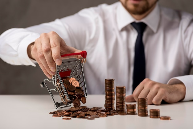 Front view of businessman spilling shopping cart of coins Free Photo