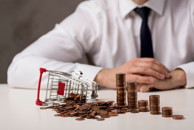 Front view of businessman with coins and shopping cart Premium Photo