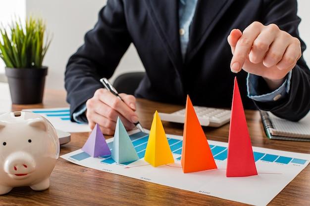 Vista frontale dell'uomo d'affari con coni colorati che rappresentano la crescita Foto Gratuite