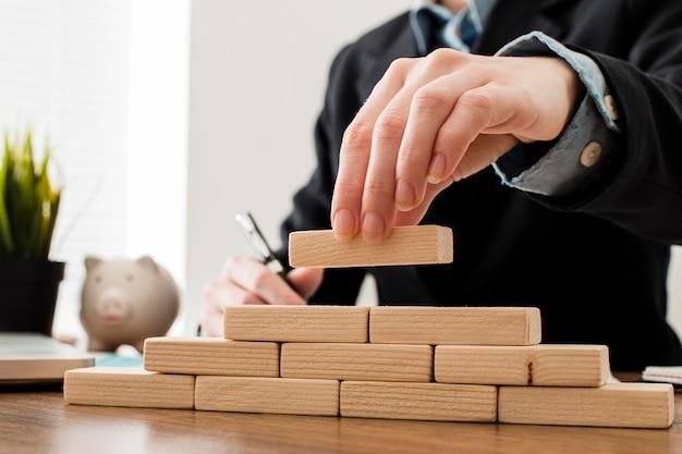 Vista frontale dell'uomo d'affari con blocchi di legno Foto Gratuite