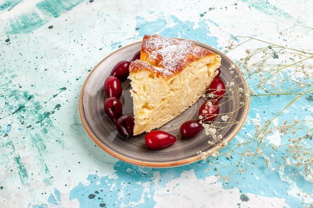 青い机の上に新鮮な赤いハナミズキと正面図のケーキスライス 無料写真