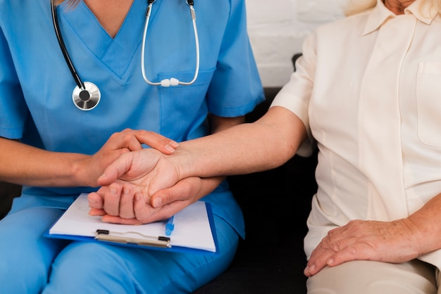 Front view caregiver holding hands with old woman close-up Premium Photo