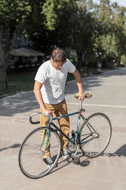 Вид спереди случайный мужчина проверяет свой велосипед Бесплатные Фотографии