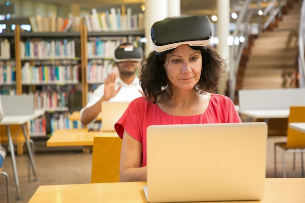 Front view of cheerful caucasian woman setting vr headset Free Photo
