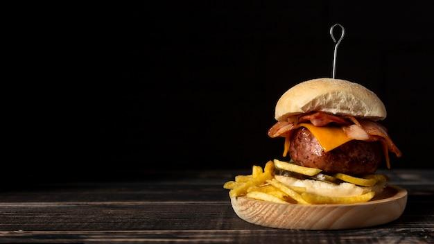 Cheeseburger e patatine fritte di vista frontale sul vassoio di legno con lo spazio della copia Foto Gratuite