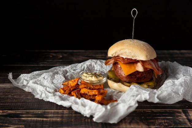 Cheeseburger vista frontale e patatine fritte con salsa Foto Gratuite