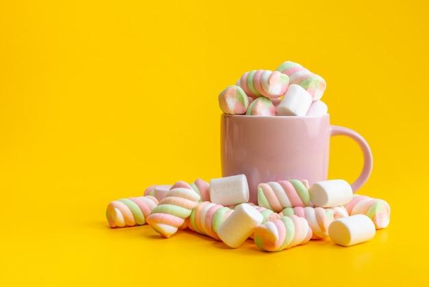 Una vista frontale mastica marmellate all'interno e all'esterno rosa, tazza su giallo, confettura di zucchero dolce Foto Gratuite