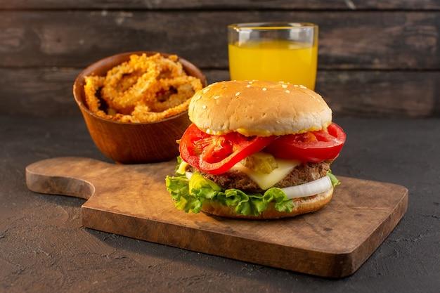 Un hamburger di pollo vista frontale con insalata di formaggio verde e succo di frutta sulla scrivania in legno e un pasto fast-food sandwich Foto Gratuite