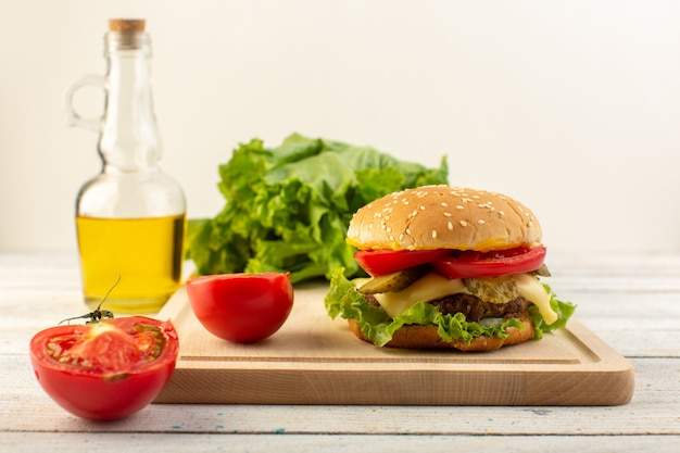 A front view chicken burger with cheese and green salad and olive oil on the wooden desk and sandwich fast-food meal Free Photo
