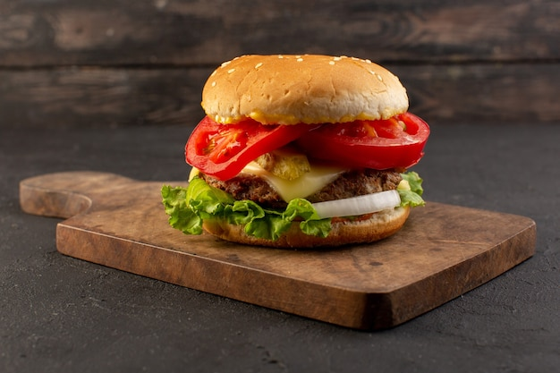 A front view chicken burger with cheese and green salad on the wooden desk and grey surface Free Photo