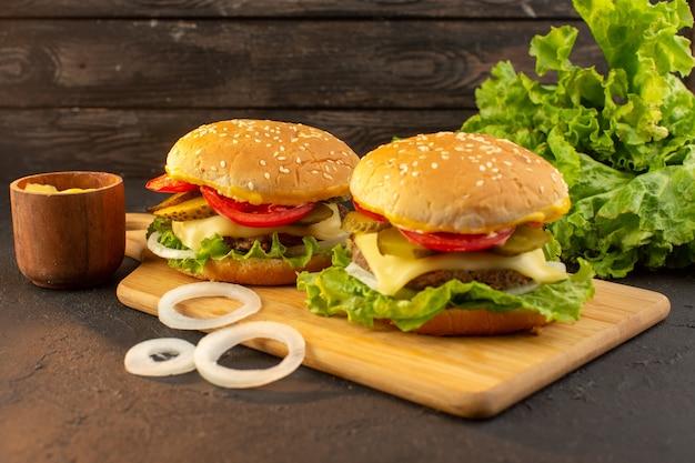 Un hamburger di pollo vista frontale con formaggio e insalata verde sulla scrivania in legno e cibo pasto fast food sandwich Foto Gratuite