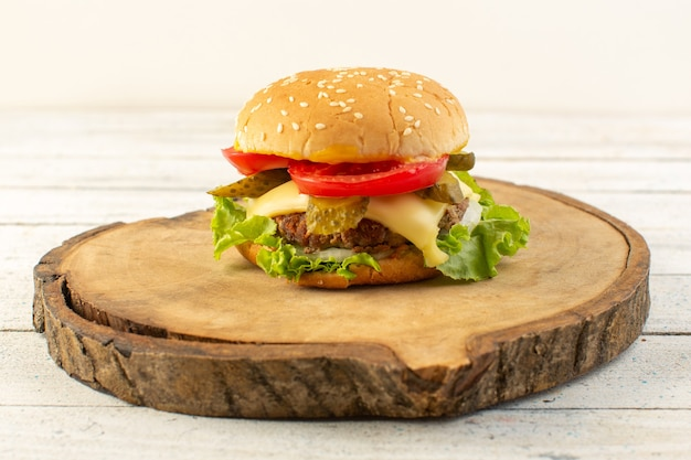 A front view chicken burger with cheese and green salad on the wooden desk and sandwich fast-food meal food Free Photo