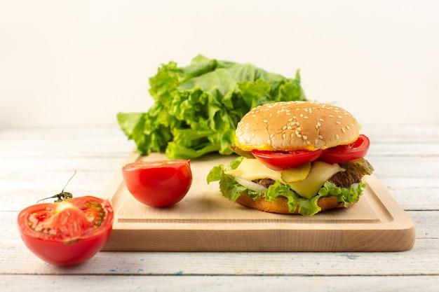 Un hamburger di pollo vista frontale con formaggio e insalata verde sullo scrittorio di legno e pasto fast-food sandwich Foto Gratuite