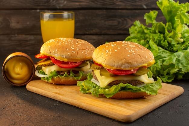Un hamburger di pollo vista frontale con succo di formaggio e insalata verde sulla scrivania in legno e un pasto fast-food sandwich Foto Gratuite