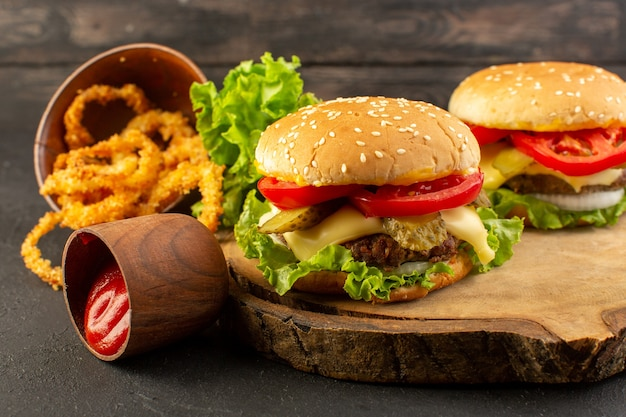 A front view chicken burgers with cheese and green salad on the wooden desk and sandwich fast-food meal food Free Photo