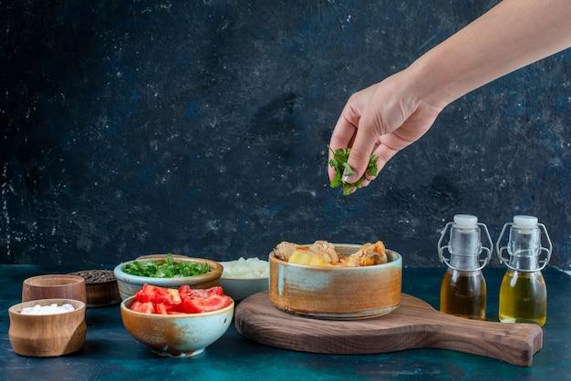 Zuppa di pollo vista frontale con patate insieme a condimenti di sale pepe verdure sulla cena di cibo di carne minestra blu scuro scrivania Foto Gratuite