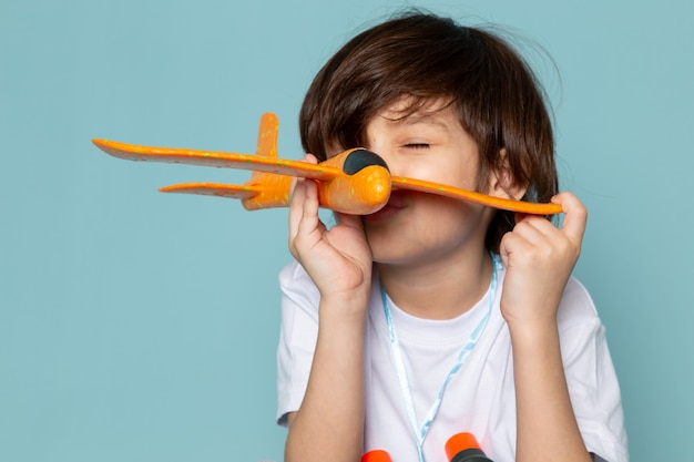 Front view child boy cute adorable playing with toy orange plane on the blue desk Free Photo