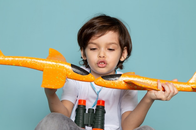 Front view child boy cute adorable playing with toy orange planes on blue Free Photo