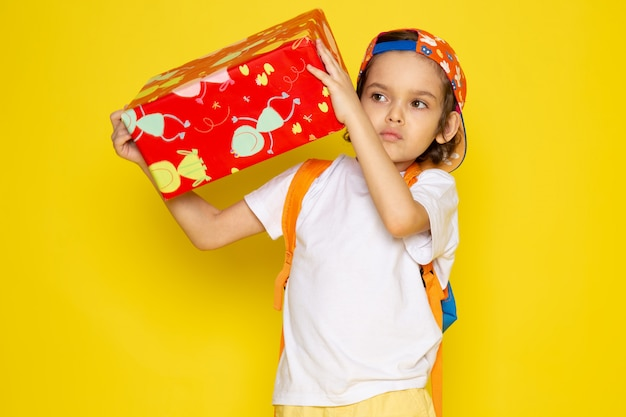 Front view child boy in white t-shirt and baseball cap holding red designed present on yellow desk Free Photo