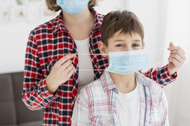 Front view of child helped by mother to put on medical mask Premium Photo