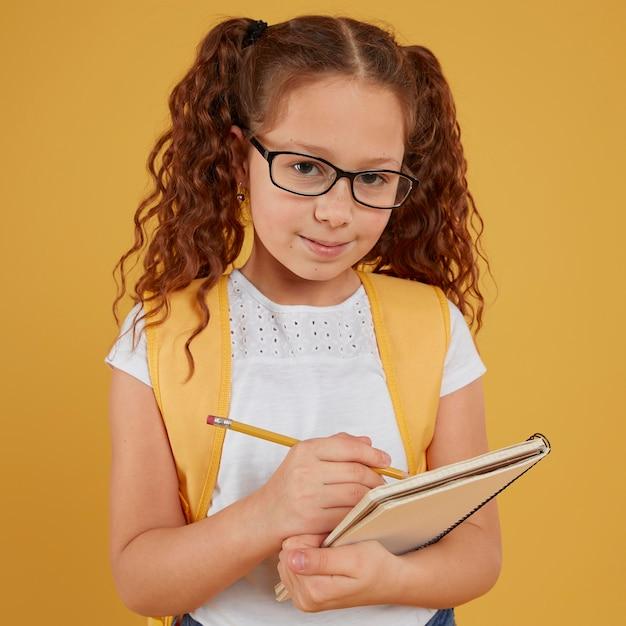 Ребенок вид спереди писать и смотреть в камеру Premium Фотографии