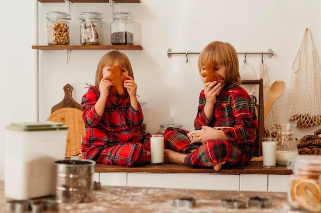 クリスマスの日に一緒にクッキーを食べる正面図の子供たち 無料写真