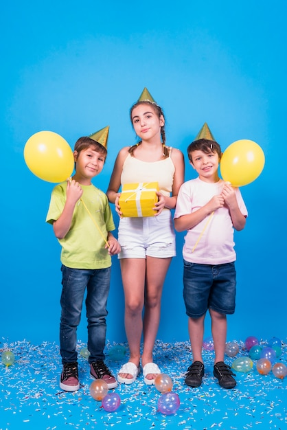 Front view of children holding balloons and gift standing on blue background Free Photo