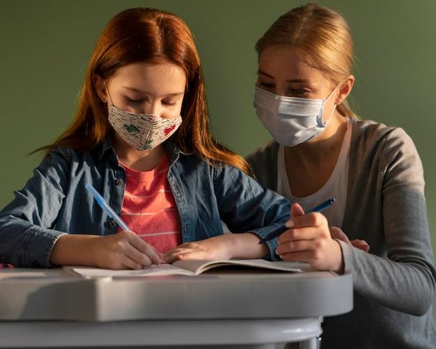 Vista frontale dei bambini che imparano a scuola con l'insegnante durante la pandemia di coronavirus Foto Gratuite