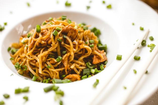 Tagliatelle cinesi di vista frontale in salsa con le cipolle verdi Foto Gratuite