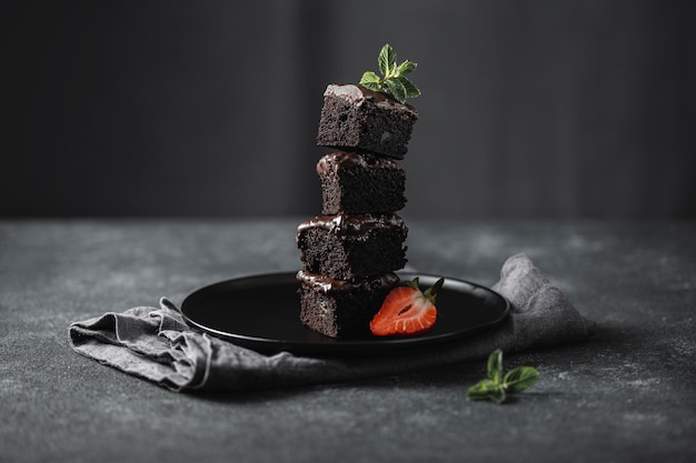 Front view of chocolate cake pieces on plate with mint Premium Photo