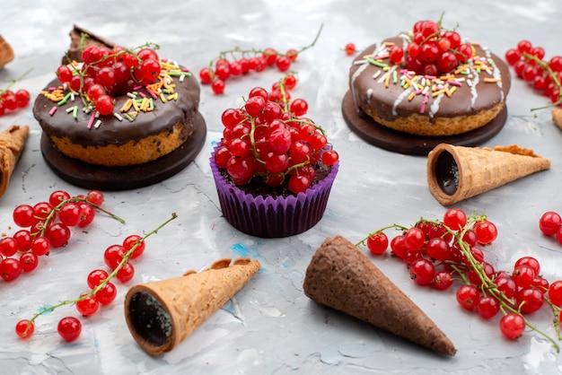 Una vista frontale torte al cioccolato con ciambelle progettate con frutta e corna sullo sfondo bianco torta biscotto ciambella al cioccolato Foto Gratuite