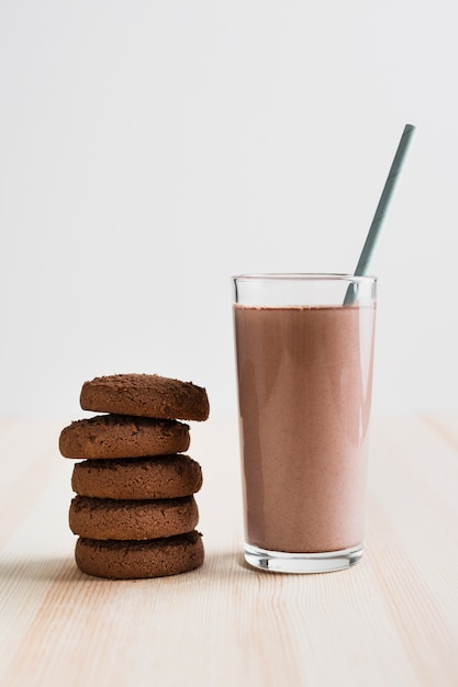 Front view chocolate milk in glass with straw and cookies Free Photo