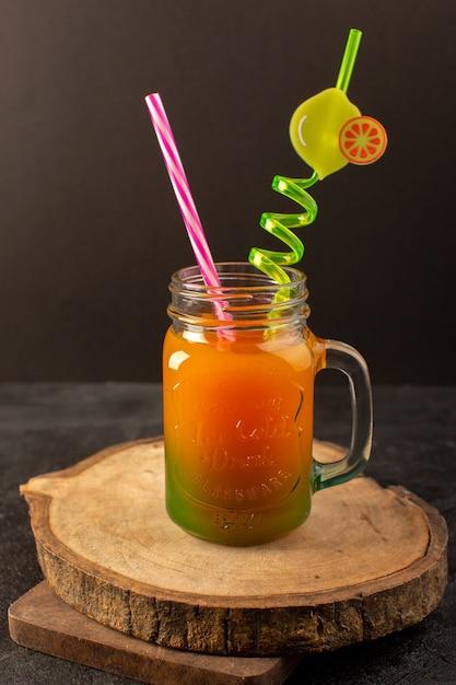 Un cocktail freddo di vista frontale colorato all'interno della latta di vetro con paglia colorata isolata sulla scrivania in legno e buio Foto Gratuite