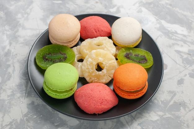 Torte colorate vista frontale con anelli di ananas secchi su superficie bianca chiara Foto Gratuite