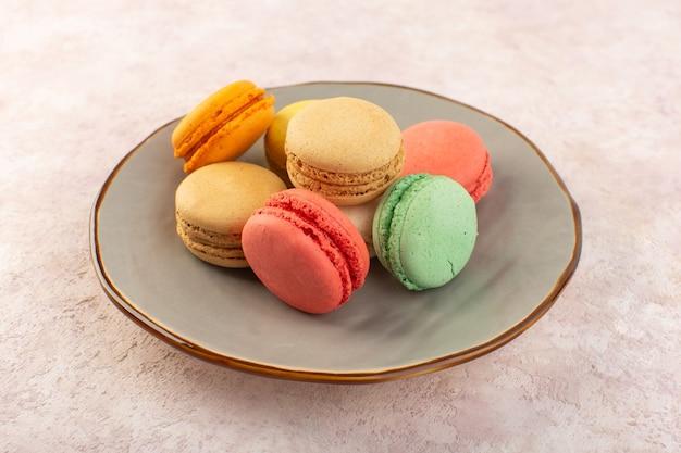 Un macarons francesi variopinti di vista frontale all'interno del piatto sulla torta dolce dello zucchero del biscotto dello scrittorio rosa Foto Gratuite