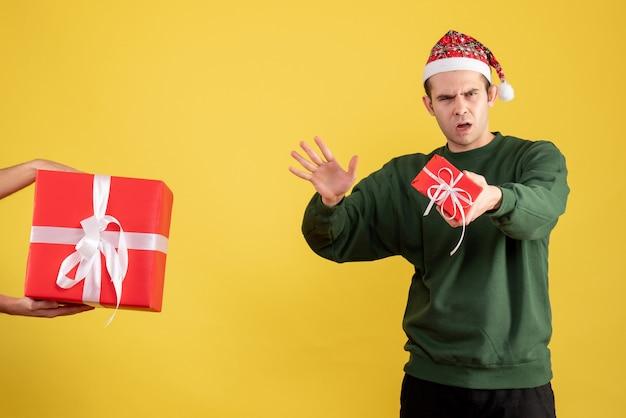 Vista frontale confuso giovane uomo il dono in mano femminile su colore giallo Foto Gratuite