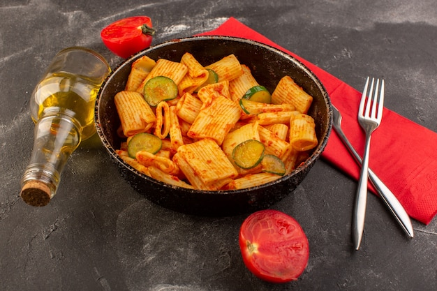 Una vista frontale ha cucinato la pasta italiana con salsa di pomodoro e cetriolo all'interno della padella sullo scrittorio scuro Foto Gratuite