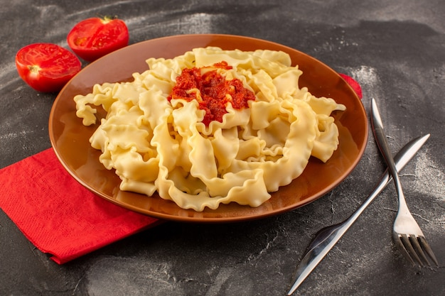 Una vista frontale ha cucinato la pasta italiana con la coltelleria della salsa di pomodoro ed i pomodori all'interno del piatto sulla superficie grigia Foto Gratuite