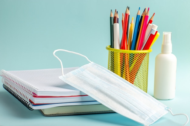 Quaderni di vista frontale e penne matite colorate maschera e spray sulla superficie blu Foto Gratuite