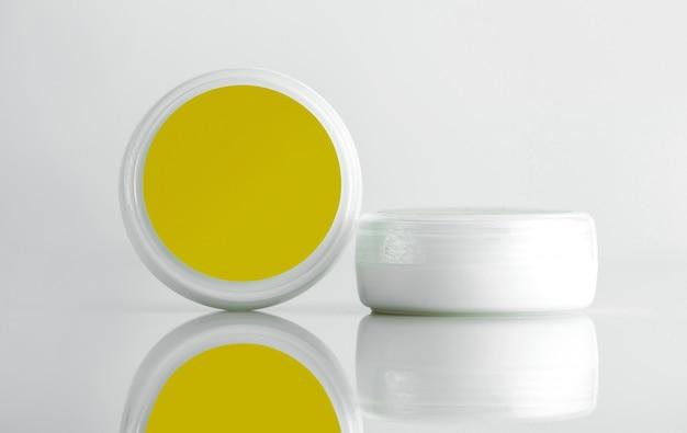 Вид спереди косметическая банка для крема белая банка с желтой крышкой Бесплатные Фотографии