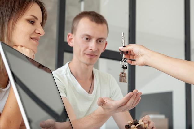 Пара вид спереди принимает ключи от нового дома Бесплатные Фотографии