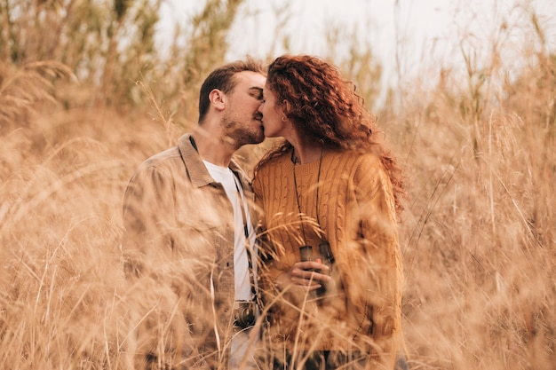 Front view couple kissing in wheat field Free Photo