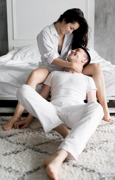Front view of couple posing next to bed at home Free Photo