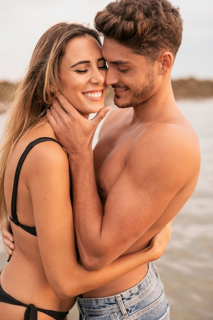 Front view of couple smiling and hugging Free Photo