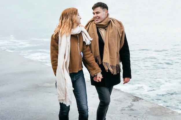 Vista frontale delle coppie che camminano mano nella mano sulla spiaggia in inverno Foto Gratuite
