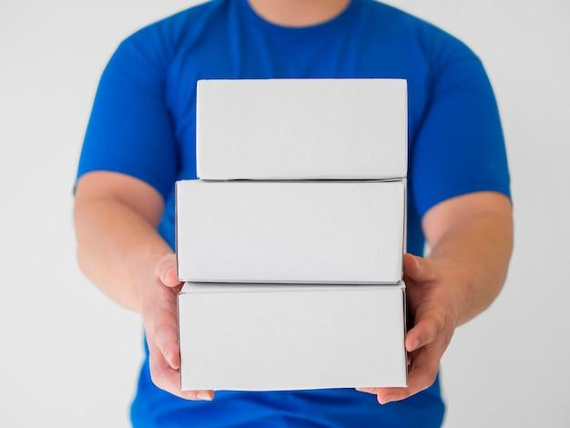 Corriere di vista frontale che tiene le scatole bianche Foto Gratuite