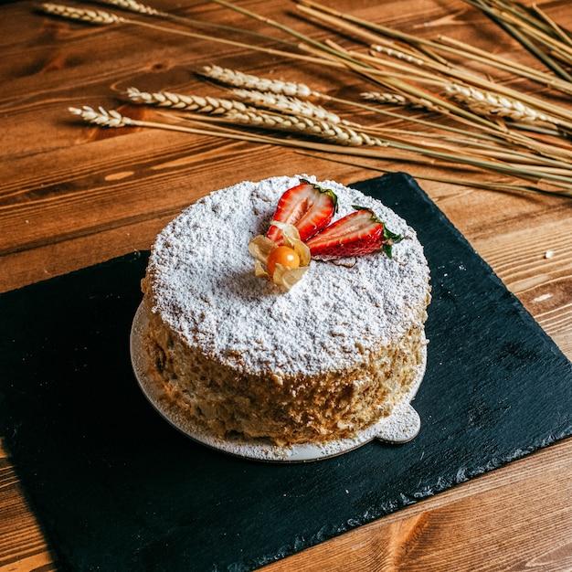 Una torta crema vista frontale decorata con deliziose fragole a fette deliziosa torta di compleanno all'interno del piatto bianco pasticceria dolcezza compleanno sullo sfondo marrone Foto Gratuite