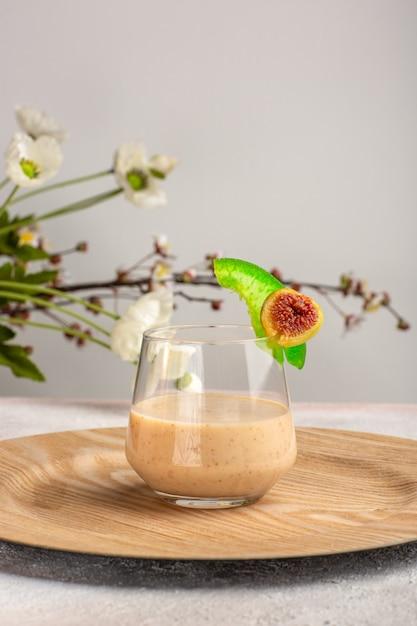 Cocktail cremoso di vista frontale all'interno del piccolo vetro sulla superficie bianca Foto Gratuite